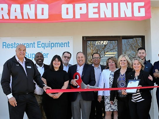 Lane & McClain Distributors owner Alan Rubin, with scissors, cuts the ribbon at the grand opening of the restaurant equipment distributor's new office at 3621 Mattox St., in East El Paso, along with company personnel, Greater El Paso Chamber of Commerce representatives, and others.