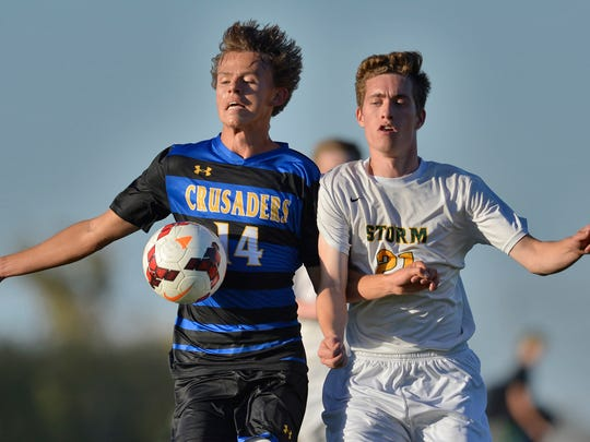 St. Cloud Cathedral's Will Torborg (14) uses his body to get control of the ball under pressure from Sauk Rapids' Kyle Conway (21) in the first half of their game Monday, Oct. 3, at Sauk Rapids-Rice High School.