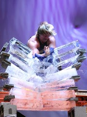 A Team Impact member splits a stack of ice blocks with his bare hand.