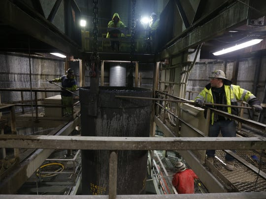 In this file photo taken Jan. 9, 2015, workers use poles to guide a bucket loaded with rock past a work platform as it is lifted out of Shaft 6B in Wappinger. The work is part of a project to repair a section of the Delaware Aqueduct that provides New York City with about half its drinking water.