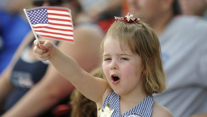 Kennedy Kemper, 3, waves an American flag during the Clawson Fourth of July Parade on Thursday, 2013.
