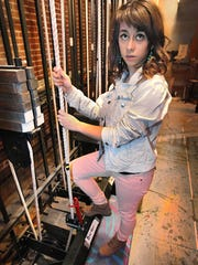 Actress Carson Meyer is pictured behind the stage at Herron High School.