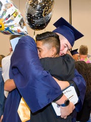 Graduates receive hugs from friends and family members