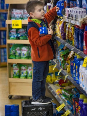Patrick Knott, 4, uses a plastic carton to give him a little more length to reach the higher shelves at his dad's market, Camron's Foodliner in Sacramento, Ky.
