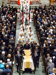 Pallbearers carry the casket of former first lady Barbara