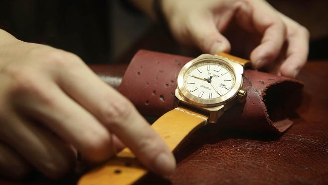 The strap of a mens bronze Switszer watch, valued at USD $850 is adjusted on the Global Line Limited Stand at the Hong Kong Watch And Clock Fair on Sept. 4, 2013 in Hong Kong, Hong Kong.