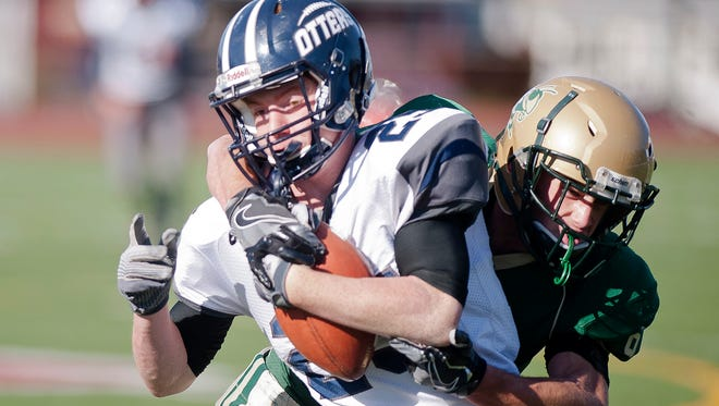 Windsor's Hunter Patenaude, right, wraps up Otter Valley's Tyson Cram after a catch during the Division III high school football championship on Saturday at Rutland High School.