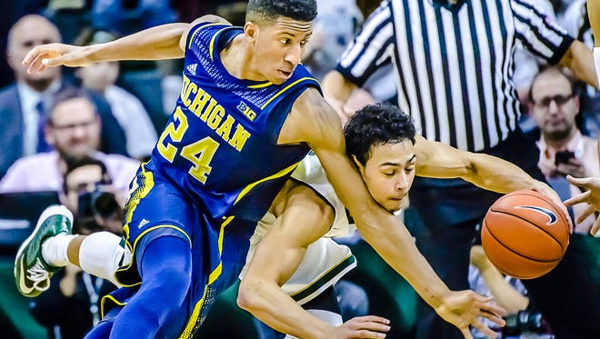 MSU's Bryn Forbes steals the ball from Michigan's Aubrey Dawkins during their game Sunday in East Lansing.