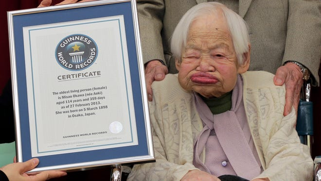 In this  Feb. 27, 2013 photo, Japan's Misao Okawa, then 114, poses with the certificate of the world's oldest woman, which was presented to her by Guinness World Records Japan Country Manager Erika Ogawa, unseen, at a nursing home in Osaka, western Japan.
