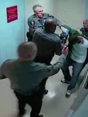 A constable at Wilmington Hospital is seen on video spraying a man as three other constables restrain him on Feb. 24.