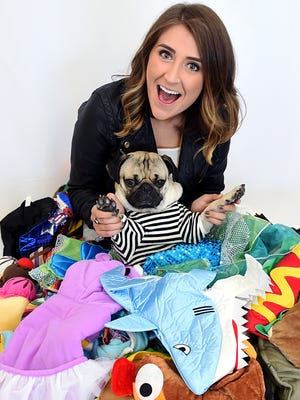 Leslie Mosier and her dog, Doug the Pug, sit in a pile of dog costumes in her Nashville apartment Monday, Sept. 14, 2015. Doug has over 100 costumes.