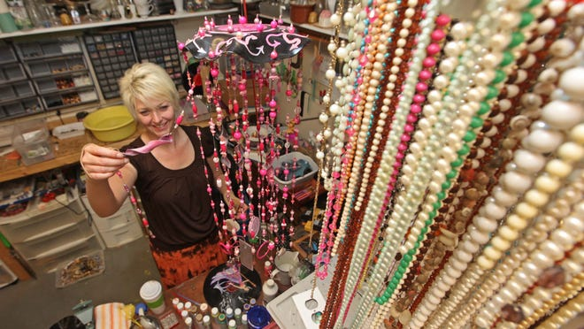 Artist Kay Martin shows a wind chime made from old jewelry and melted records.