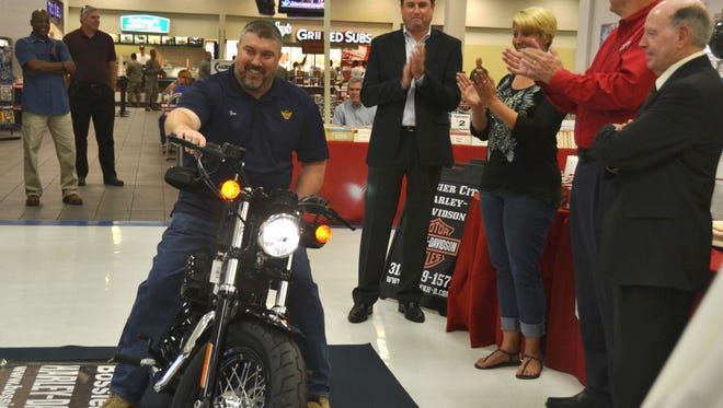 """Retired U.S. Air Force Maj. Shawn """"Goose"""" Gander tries out the Harley-Davidson motorcycle he won Friday in an Army & Air Force Exchange Service contest."""