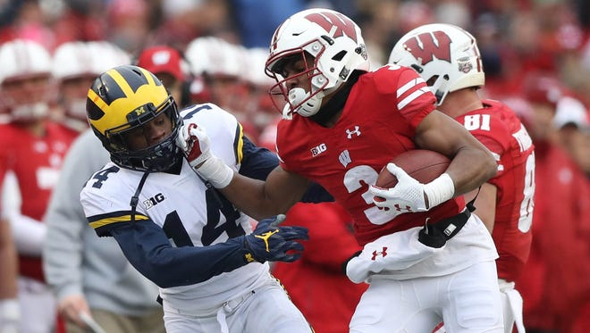 Michigan's Josh Meetellus tackles Wisconsin's Kendric Pryor during the first quarter Saturday, Nov. 18, 2017, at Camp Randall Stadium in Madison, Wis.