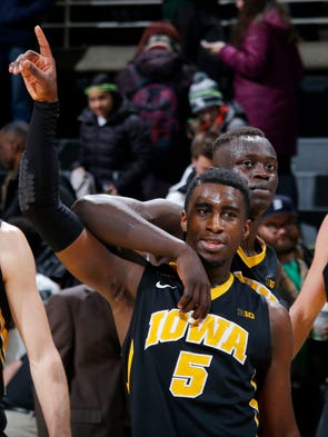 Iowa's Anthony Clemmons (5) and Peter Jok celebrate