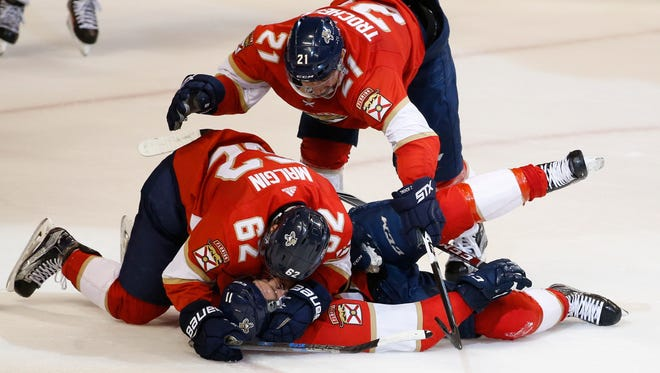 Florida Panthers centers Denis Malgin (62) and Vincent Trocheck (21) pile on top of left wing Jonathan Huberdeau after Huberdeau scored the winning goal.