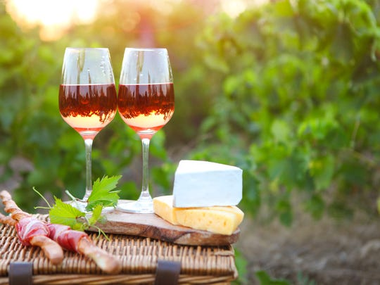 Two glasses of rose wine with bread, meat, grape and cheese laid out on a picnic basket. Rose wine is ideal for a picnic setting.