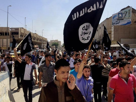 Demonstrators chant pro-Islamic State slogans as they carry the group's flags in Mosul, Iraq, in 2014.