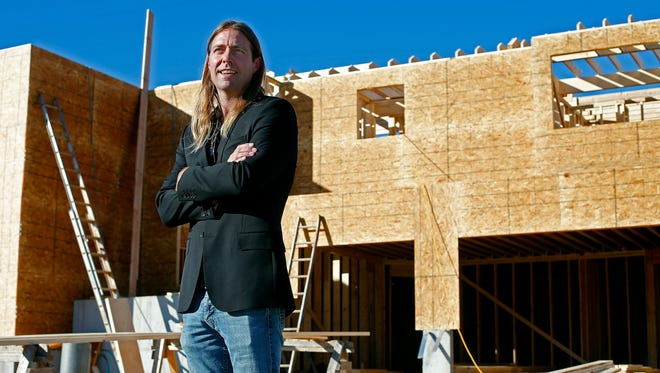 Home developer Shawn Turner stands in front of one of his properties in the Columns subdivision in Nixa, Mo. on Nov. 10, 2015. After a disappointing 2014 in which he only sold 96 houses, he is riding the high Christian County growth as he sold his 100th house of the year in October.
