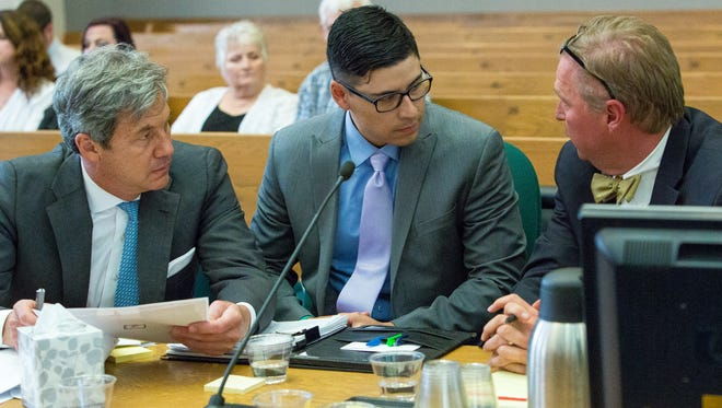 Defendant Tai Chan talks with his attorneys John Day, left, and Thomas Clark at his trial in 3rd Judicial District Court on Monday May 23, 2016. Chan, a former Santa Fe County sheriff's deputy, is charged with the first degree murder of fellow deputy Jeremy Martin at Hotel Encanto in 2014.