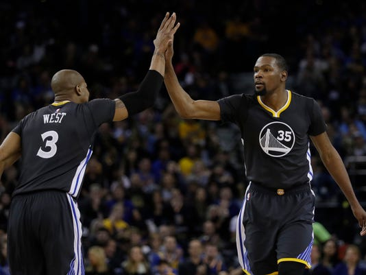 Golden State Warriors' Kevin Durant, right, celebrates with teammate David West (3) after Durant scored during the second half of an NBA basketball game against the New Orleans Pelicans on Saturday, April 8, 2017, in Oakland, Calif. (AP Photo/Marcio Jose Sanchez)