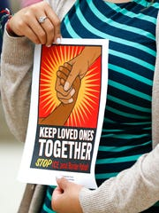 A poster held during the community gathering Monday at the Indiana Statehouse.