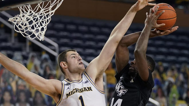 Central Florida forward Ibrahim Famouke Doumbia (14) shoots over the defense of Michigan center Hunter Dickinson (1) during the first half of an NCAA college basketball game, Sunday, Dec. 6, 2020, in Ann Arbor, Mich.