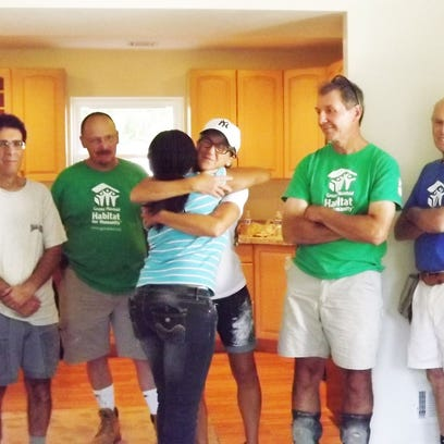 Volunteers and the new home owner of Habitat for Humanity's