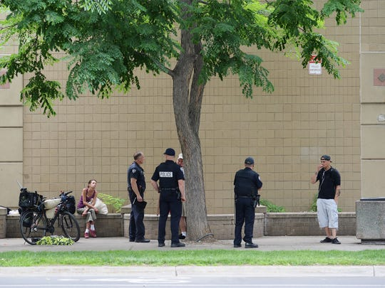 Police stop to talk with people on the east side of the Old Town Safeway, while on patrol in Old Town Fort Collins on Thursday, June 30, 2016.