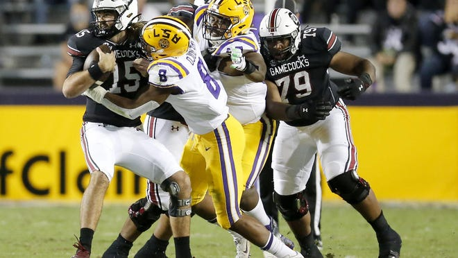 South Carolina quarterback Collin Hill (15) is brought down by LSU linebacker BJ Ojulari (8) during the first half of an NCAA college football game in Baton Rouge, La., Saturday, Oct. 24, 2020.