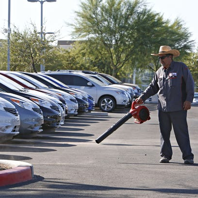 Jesus Lopez cleans the car lot at Coulter Nissan at