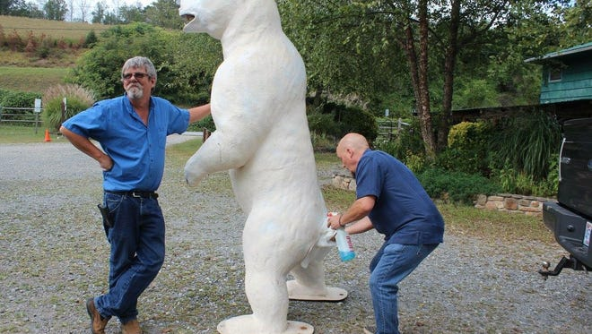 "Polar bear owner Lane Reid, left, supports ""The Bear"" while his business partner, Joey Cain, cleans the fiberglass animal's derriere. ""The Bear,"" as they call it,  often hangs out at their shop on Haywood Road, Image 420 Screen Printing."