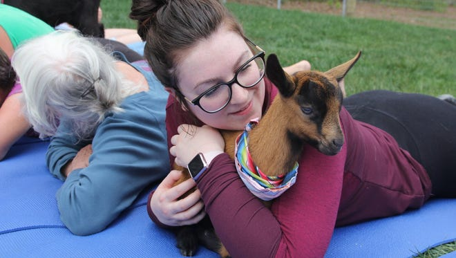 Shelby Valentine cozies up with one of the kids at goat yoga.