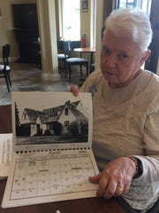 Carol Zolkoske displays a calendar photo of the Eugene
