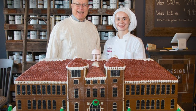 "Chancellor Bernie Patterson poses with an ""Old Main"" gingerbread house decorated by Megan Herman of Kochie's Cookies of Stevens Point. A silent auction was held for the 4.5-foot long model of the University of Wisconsin-Stevens Point's administrative building, built in 1894. John Noel was the high bidder at $250, and Kochie's Cookies matched the bid. The $500 was donated to Operation Bootstrap. Kids at the Boys and Girls Club of Stevens Point got the sweetest end of the deal: The giant gingerbread house was delivered there Wednesday."