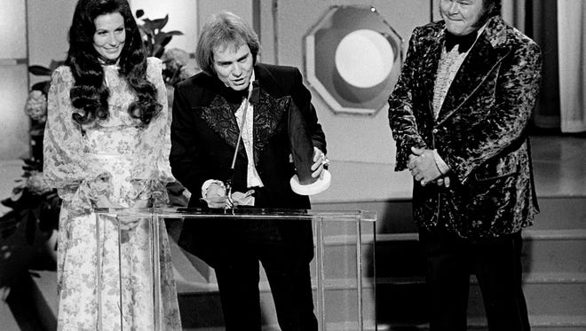 """Songwriter Kenny O'Dell, center, accepted the Song of the Year award for his blockbusting song, """"Behind Closed Doors,"""" at the seventh annual Country Music Awards show at the Grand Ole Opry House Oct. 15, 1973. Looking on are presenters Loretta Lynn, left, and Roy Clark."""
