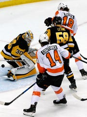 A shot by Philadelphia Flyers' Shayne Gostisbehere gets through the pads of Pittsburgh Penguins goaltender Matt Murray (30) with Flyers' Nolan Patrick (19) providing a screen during the first period in Game 2 of an NHL first-round hockey playoff series against the in Pittsburgh, Friday, April 13, 2018. (AP Photo/Gene J. Puskar)