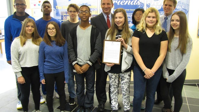 Harrison Township Mayor Lou Manzo (center) poses with an eighth grade civics class at Friends School Mullica Hill. The students and their teacher Brad Gibson (right) helped get an ordinance passed to lower the speed limit near the school.