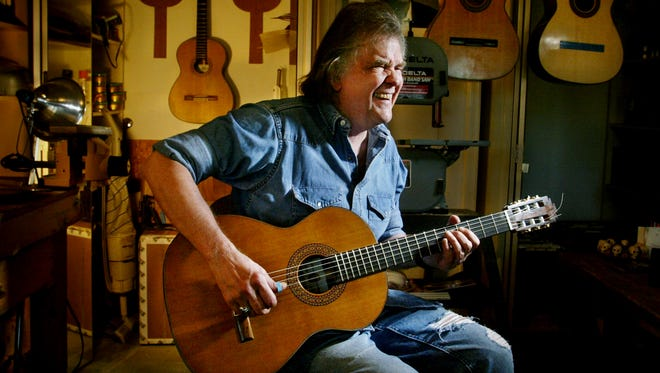 Guy Clark takes his No. 8 handmade guitar for a spin for the first time in the basement shop of his home Dec. 27, 2003.