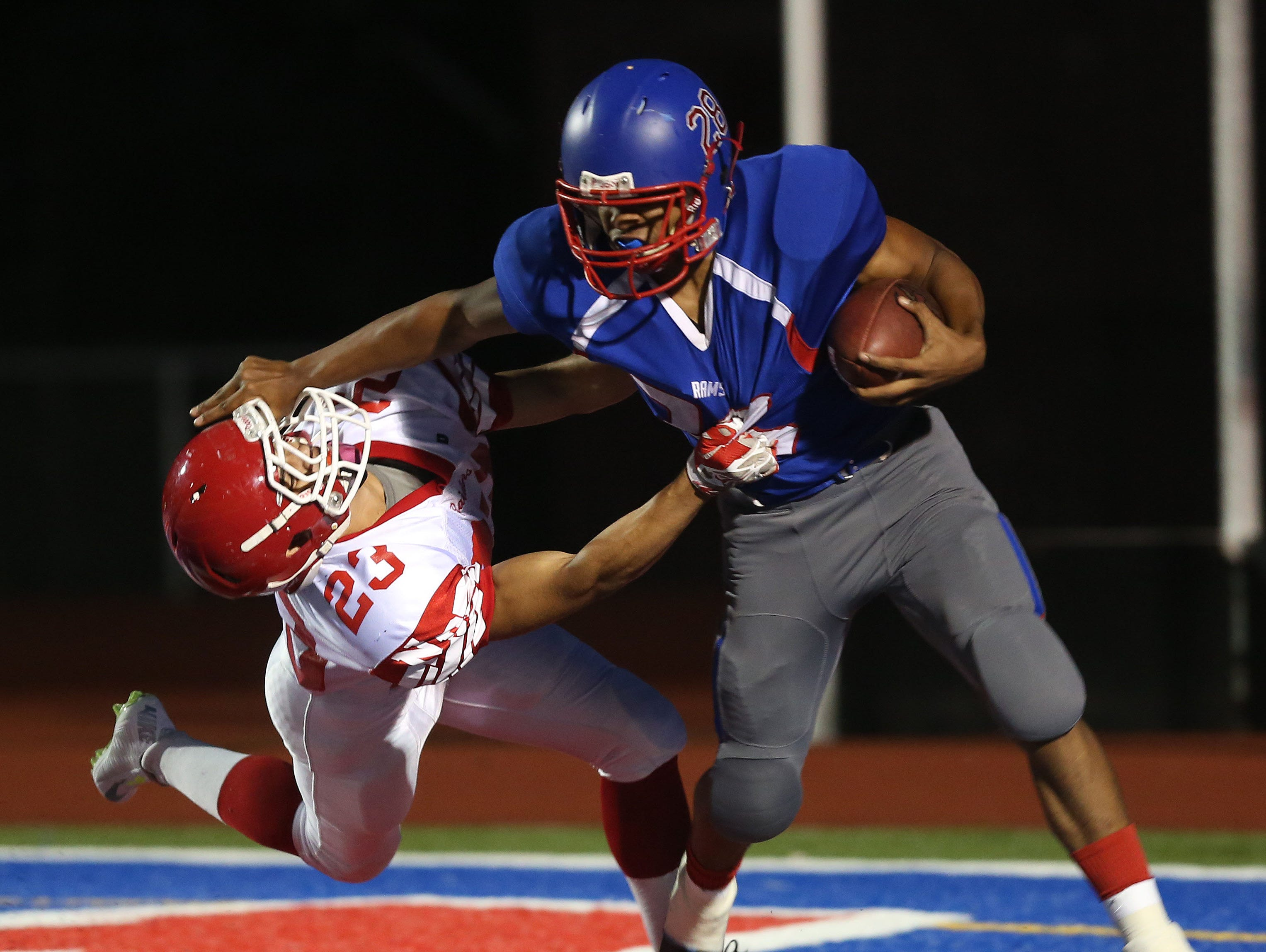 Carmel's Kasey Correa (28) breaks away from North Rockland's Nick Cortez (23) on a big first half run during football action at Carmel High School Sept. 25, 2015