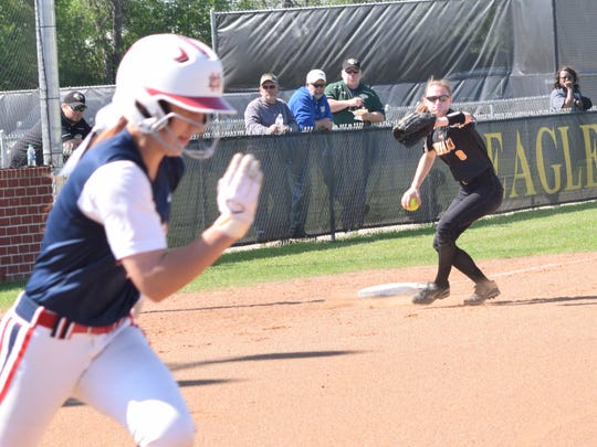 Menard's third baseman Maddie Smith (8, right) throws to first for an out against North Desoto's Amber Giddens (4, left).