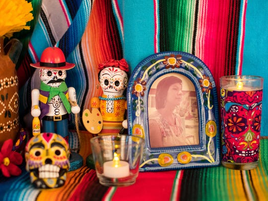 A photo of a deceased loved one sits on a Dia de los Muertos altar display