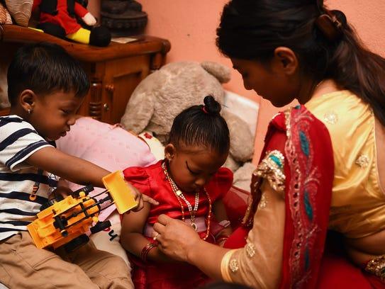Trishna Shakya, 3, sits with her twin brother Krishna