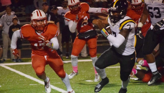 Tioga's Corbin Malone (17, left) goes after Neville quarterback Jaiden Cole (7, right) who runs the ball for a first down in Week 8.