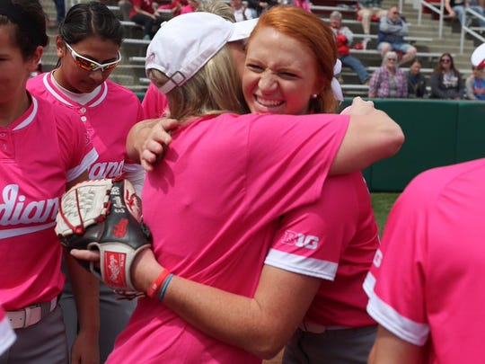 Julie (left) and Emily Goodin hug before Indiana University's Think Pink softball game on Saturday.