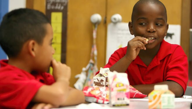 Rachel Denny Clow/Caller-Times Evans Elementary School second-graders Rocky Garcia (left) and Marcell Davis (both 7) eat breakfast in their classroom in September 2008. A program that feeds students breakfast before class begins began the previous week.