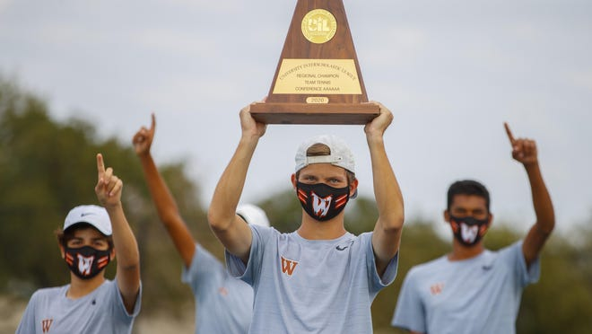 Westwood's Nick Pesoli holds up the regional trophy after the Westwood tennis team beat  Westlake at the Class 6A Region IV title duel Tuesday at Vandegrift High School.