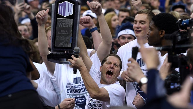 Nevada head coach Eric Musselman, middle, celebrates with his players and fans following the Wolf Pack's victory over Colorado State to win the Mountain West regular-season championship Saturday at Lawlor Events Center.