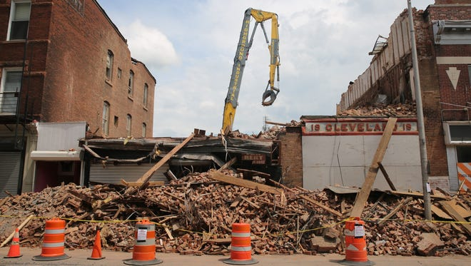 A pile of debris and a building facade rest where 17 and 19 Academy St. used to stand tall. Crews from Highground Industrial finished demolition work on Friday following last week's building collapse.