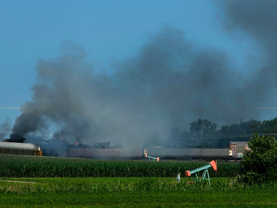 Derailed CSX train cars continue to burn before 9 a.m., Monday morning after an explosion of a propane tank at about 7 p.m. Sunday evening, June 17, 2018. Law enforcement said two of the cars were carrying French fries and those are creating most of the smoke from the remaining two fires burning. CSX is allowing the fires to burn themselves out.